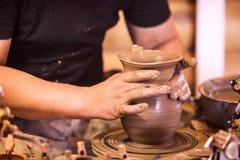 Конец-вверх рук делая гончарню на колесе Стоковая Фотография