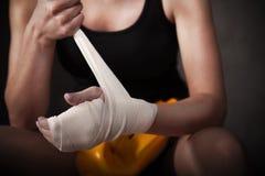 女性在腕子的拳击手佩带的白色皮带 免版税图库摄影
