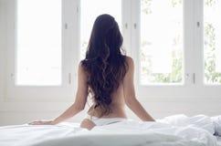 在床上的性感的女孩后面 图库摄影