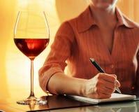 品酒。做在笔记本的斟酒服务员笔记 免版税库存图片