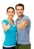 Το ευτυχές ζεύγος που παρουσιάζει αντίχειρες υπογράφει επάνω Στοκ Εικόνες