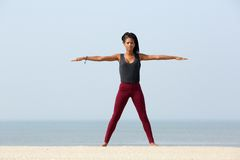 在海滩的瑜伽舒展 免版税库存图片