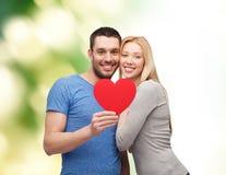 拿着大红色心脏的微笑的夫妇 免版税图库摄影