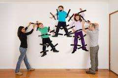 黏附孩子的父母对墙壁笑话 免版税库存照片