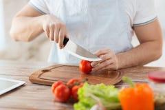 男性手切口蕃茄在船上与刀子 免版税库存照片