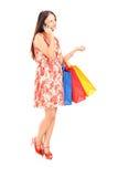 有购物袋的妇女谈话在电话 免版税图库摄影