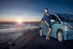 Изумительная женщина красоты представляя рядом с ее автомобилем морем на заходе солнца Стоковые Изображения