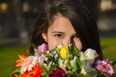 Χαριτωμένη νέα γυναίκα που κρύβει το πρόσωπό της πίσω από την ανθοδέσμη Στοκ Φωτογραφίες