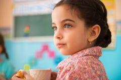有杯子的逗人喜爱的西班牙女孩在托儿的牛奶 免版税库存照片