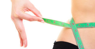 减重。在妇女身体的绿色测量的磁带 免版税库存照片