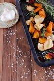 与海盐、迷迭香和大蒜的健康菜芯片在土气背景的一个金属盘子 库存图片