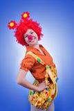 蓝色背景的愉快的妇女小丑 库存照片