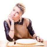изображение красивой молодой привлекательной белокурой женщины держа вилку в ее руке смотря вверх, пустая плита изолированная на б Стоковые Изображения