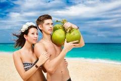在热带海滩的年轻爱恋的愉快的夫妇,用椰子 免版税库存图片