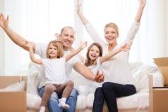 微笑的父母和两个小女孩在新的家 免版税图库摄影