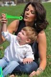 母亲和儿子吹的泡影 免版税库存图片