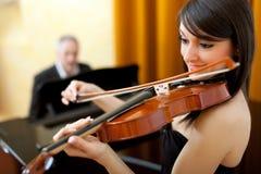 女性小提琴手和男性钢琴演奏家 免版税库存图片