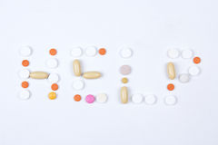 帮助词文本由五颜六色的片剂、药片和胶囊做成 库存照片