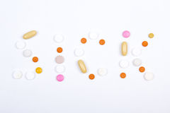 Άρρωστο κείμενο λέξης φιαγμένο από ζωηρόχρωμες ταμπλέτες, χάπια και κάψες Στοκ Εικόνα