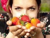 美丽的女孩在春天(焦点的嗅到新鲜的草莓 免版税库存照片