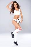 Προκλητική όμορφη τοποθέτηση γυναικών με μια σφαίρα ποδοσφαίρου Στοκ φωτογραφία με δικαίωμα ελεύθερης χρήσης