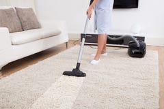 佣人有吸尘器的清洁地毯 免版税图库摄影