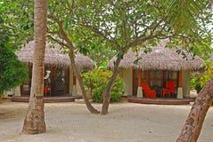 与大量的热带海滩村庄在白色美好的沙子的树 免版税图库摄影