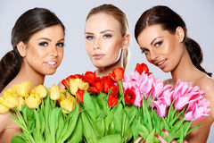 有新鲜的春天郁金香的三名美丽的妇女 免版税库存图片