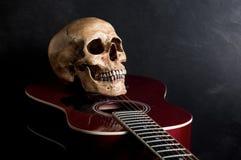 有声学吉他的头骨 免版税库存图片