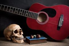 有声学吉他的头骨 库存照片
