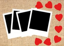 红色心脏和照片卡片在大袋帆布粗麻布背景 免版税库存照片