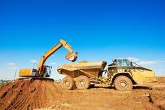 轮子装载者挖掘机和卸车倾销者 免版税库存图片