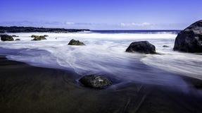 黑沙子海滩。 库存图片