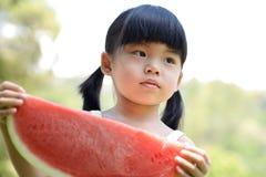 孩子用西瓜 免版税库存图片