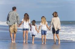 家庭做父母走在海滩的女孩孩子 免版税库存图片