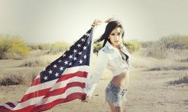 拿着美国国旗的妇女佩带的牛仔布衬衣 库存图片