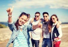 有外面耳机和朋友的十几岁的女孩 库存图片