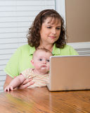 抱着婴孩的母亲,当研究计算机时 免版税库存图片