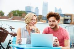 年轻夫妇坐屋顶大阳台使用膝上型计算机 免版税库存图片