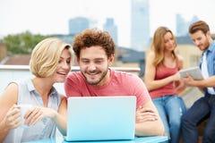 屋顶大阳台的朋友使用膝上型计算机和数字式片剂 免版税库存照片