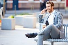 在公园长椅的商人用使用手机的咖啡 免版税库存图片