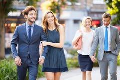 一起走通过城市公园的年轻企业夫妇 库存图片