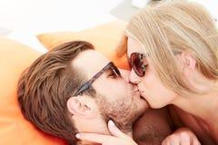 年轻夫妇在度假放松由游泳池的 免版税库存照片