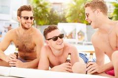 三个年轻男性朋友在度假由一起水池的 免版税库存照片