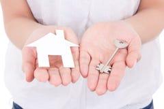 纸房子和金属钥匙在女性手上 免版税库存图片