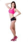 一名年轻美丽的运动的妇女佩带的体育短裤和上面的演播室画象 免版税库存图片