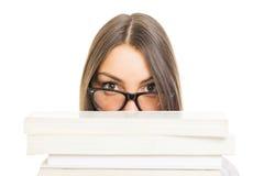 戴掩藏在书后的眼镜的学生女孩 免版税图库摄影