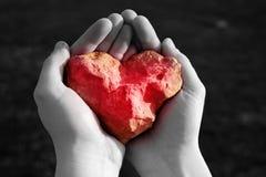 石光亮的红色心脏在手中 免版税库存照片