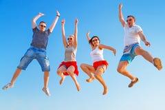 跳跃充满幸福的小组朋友 免版税库存图片
