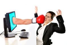 有计算机的妇女通过拳击手套社会媒介网络围攻击中了 免版税图库摄影